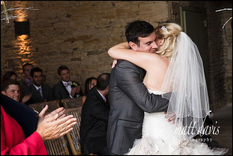 Bride kissing groom at Stone Barn