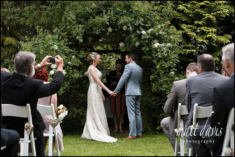 outdoor wedding ceremony at Friars Court under the rose arbor