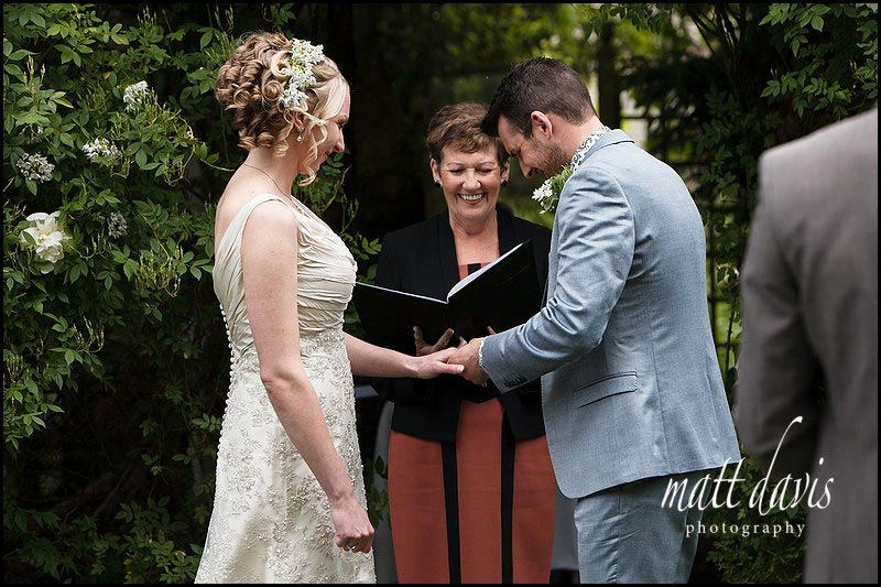 wedding ceremony outdoors at Friars Court under the rose arbor