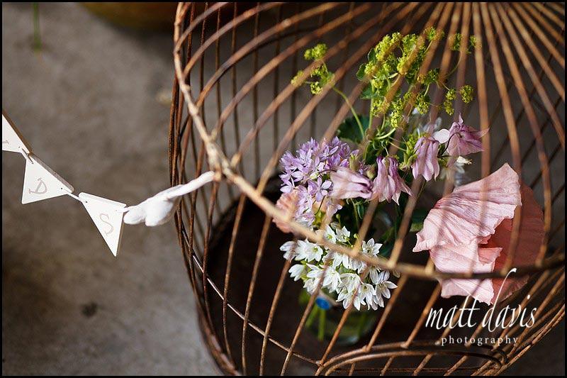 flowers in vintage birdcage at wedding