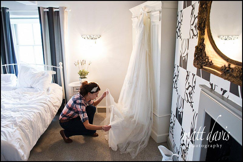 Bride with dress hung on wardrobe