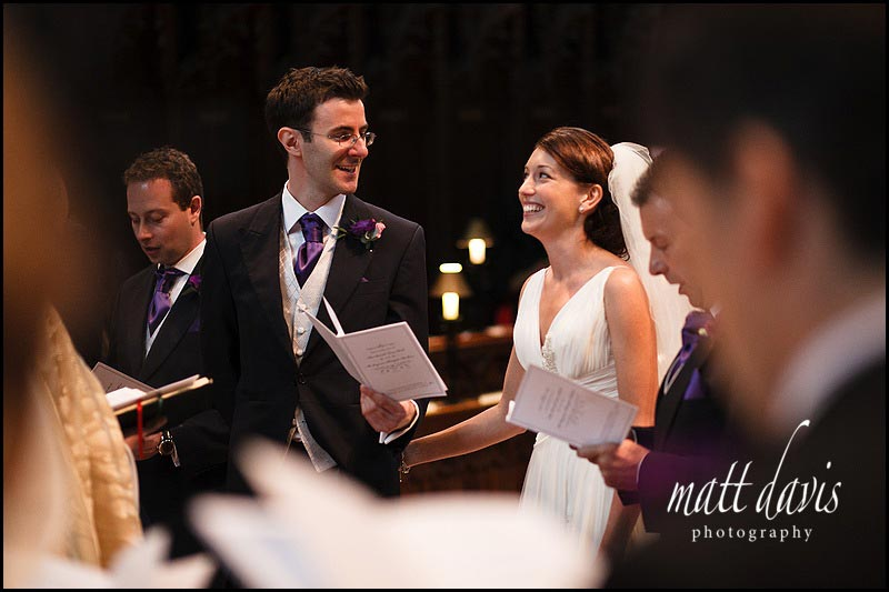bride and groom signing during a hymn at Gloucester Cathedral