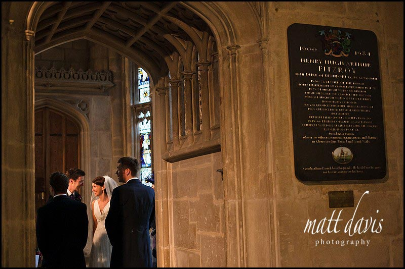 bride smiling at groom during signing of the register in Gloucester Cathedral