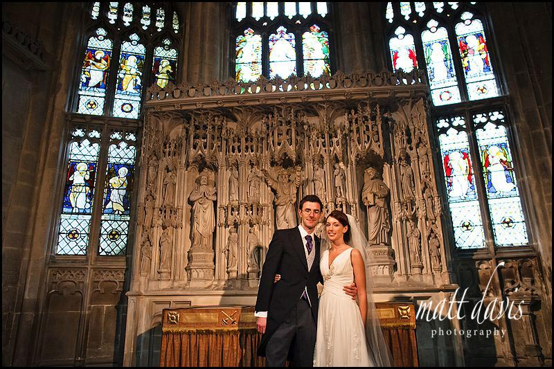 bride and groom in front of stained glass window at Gloucester Cathedral