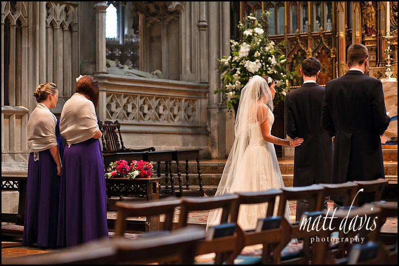 tender moment during wedding ceremony at Gloucester Cathedral