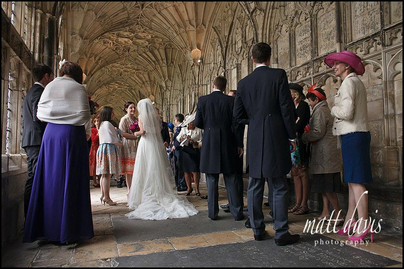 Wedding guests in the cloisters at Gloucester Cathedral