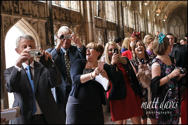 Wedding guests laughing in the cloisters at Gloucester Cathedral