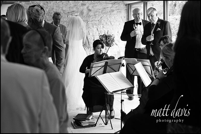 Wedding drinks reception indoors at Kingscote Barn with quartet playing
