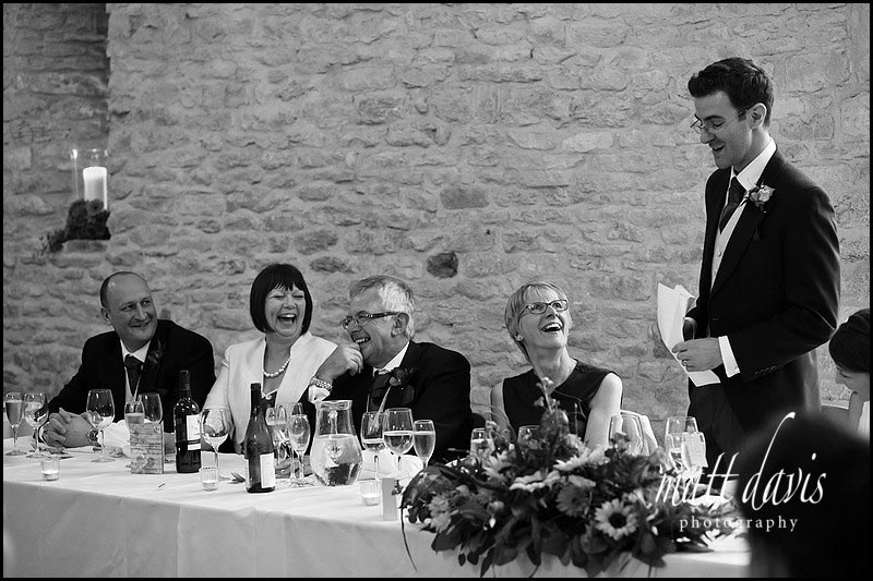 family laughing during wedding speeches at Kingscote Barn