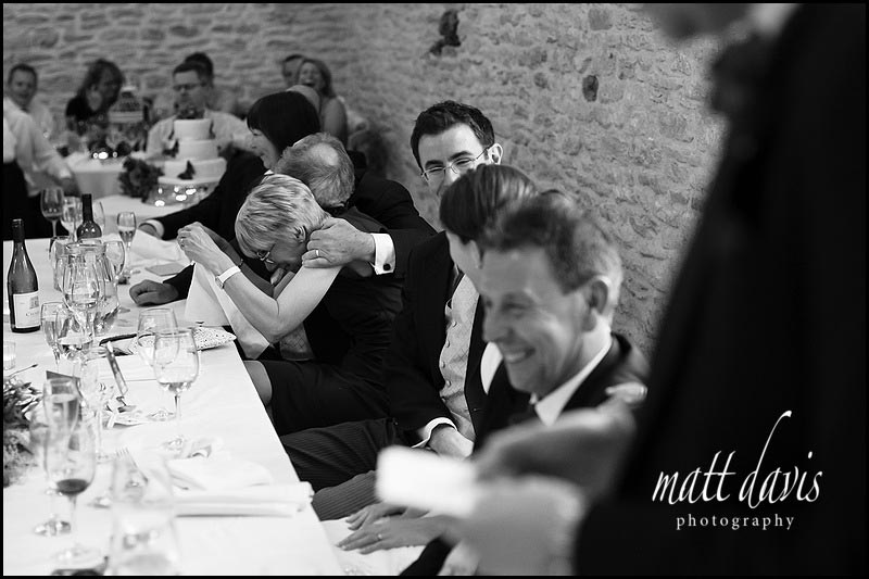 Wedding speeches at Kingscote Barn with guests laughing