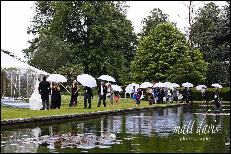 Wedding guests walking around Sudeley castle pond