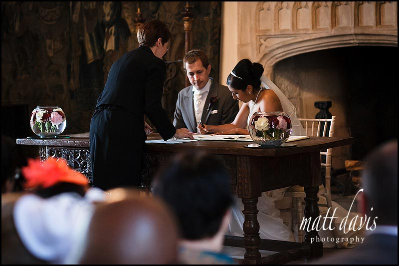 Married couple sign the wedding register during civil ceremony at Berkeley Castle