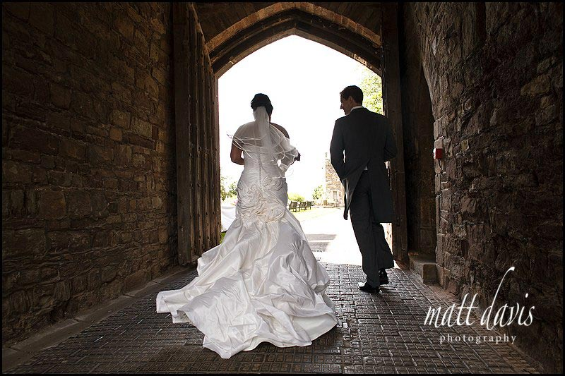wedding couple walking through an archway at Berkeley Castle