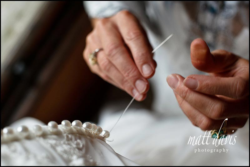 buttons being sewn onto a weding dress