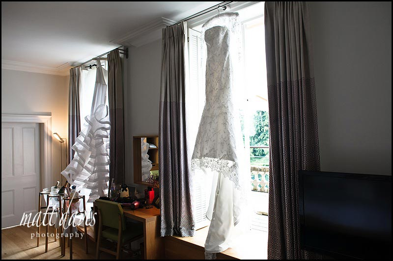 Two wedding dresses hung in a window at Cowley Manor