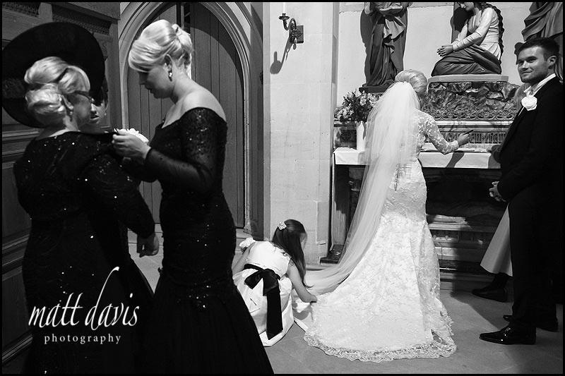 Bridesmaid adjusting brides dress whilst signing the wedding register