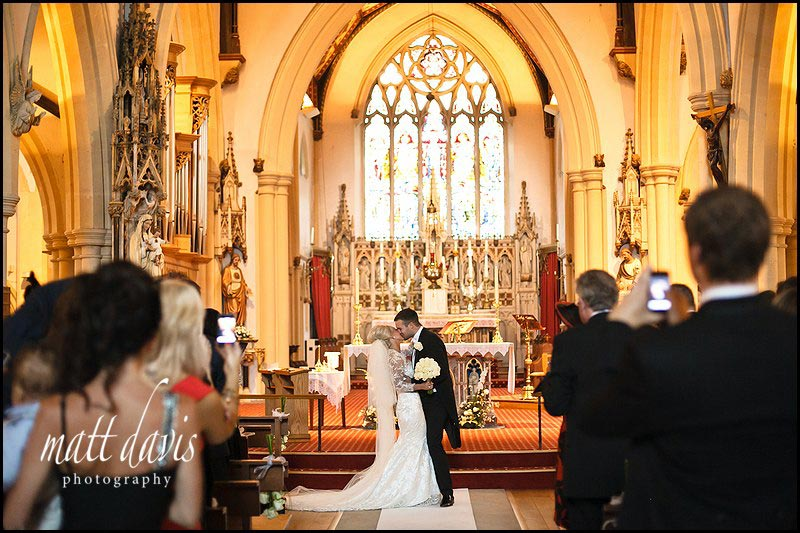Wedding couple kiss inside St Gregory's Church, Cheltenham, Gloucestershire