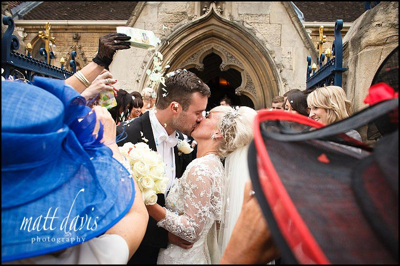 Couple kiss at St Gregory's Church, Cheltenham whilst confetti is thrown
