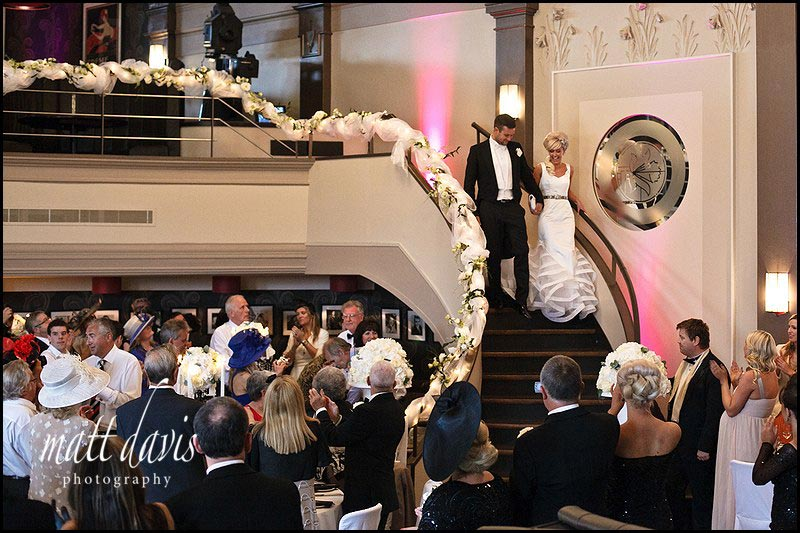 A wedding couple walking down the stairs at the daffodil Cheltenham