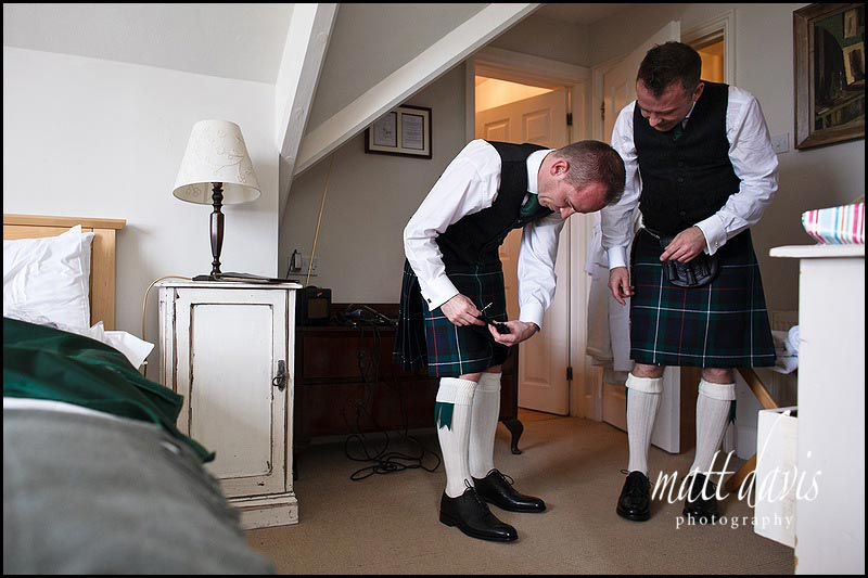Groom and best man doing up their kilts
