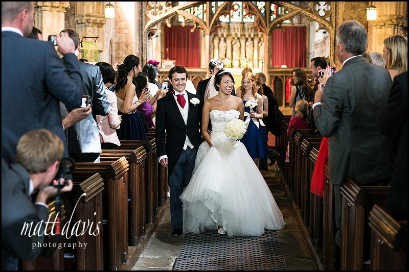 wedding photo of bride and groom leaving Berkeley Church, Gloucestershire