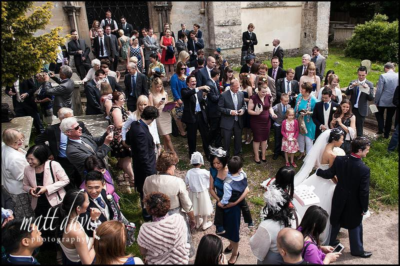 wedding guests outside Berkeley Church, Gloucestershire
