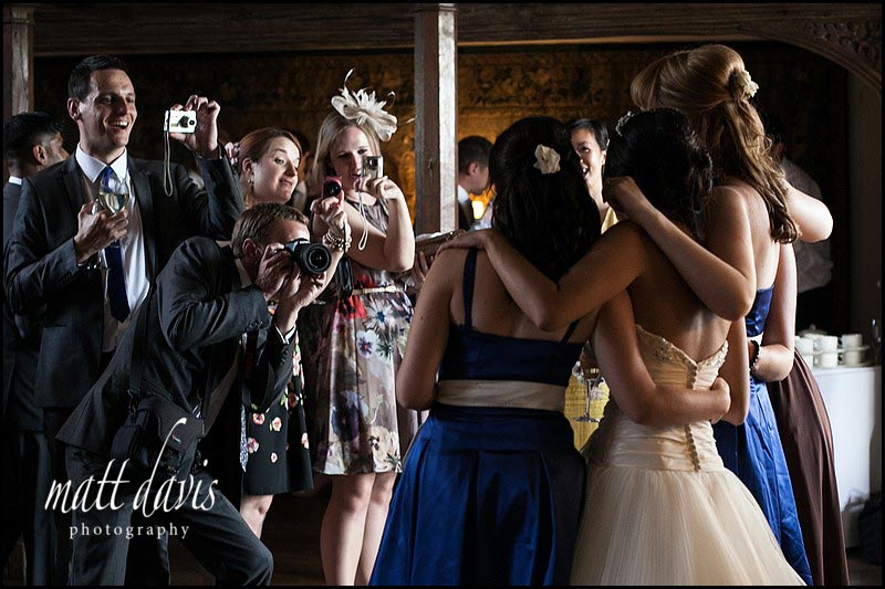 wedding guests photographing the bride and bridesmaid inside Berkeley Castle