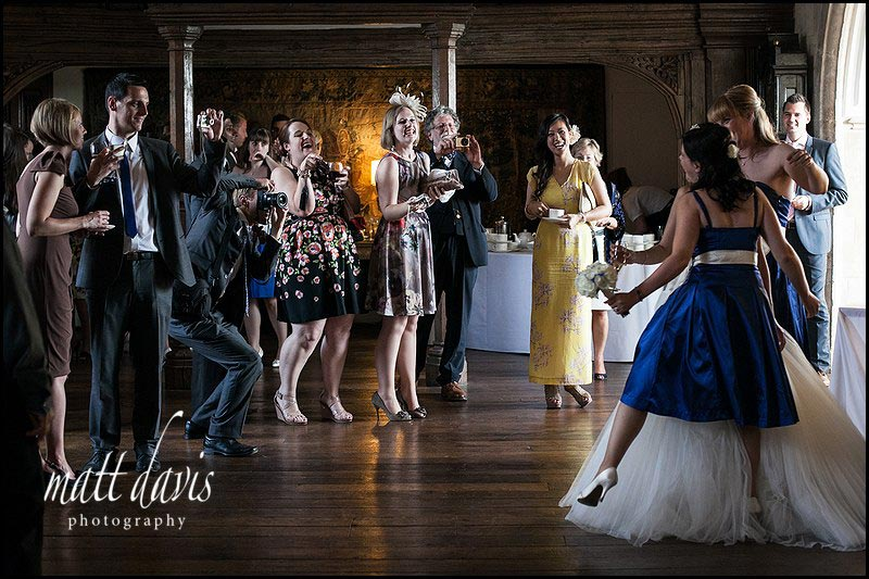 wedding guests photographing the bride & bridesmaid inside Berkeley Castle