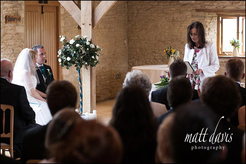 Readings during a wedding ceremony inside Kingscote Barn