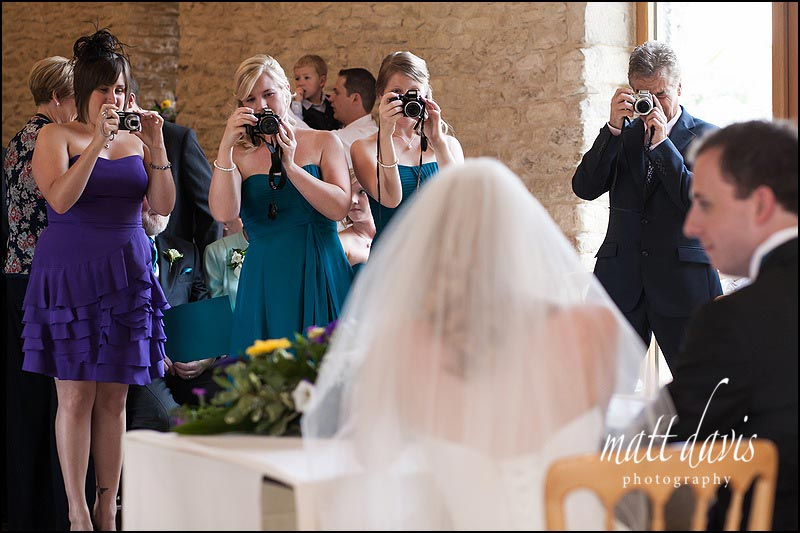 Wedding guests taking photos inside Kingscote Barn