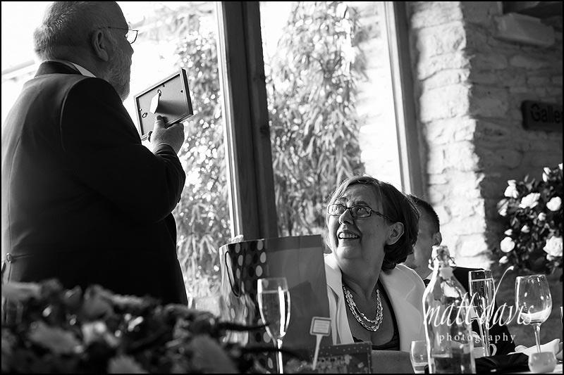B&W wedding photos at Kingscote Barn during speeches