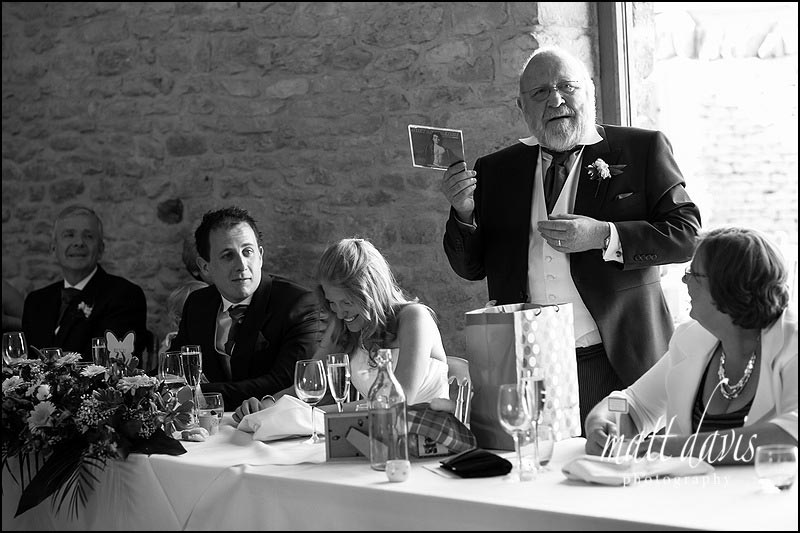 Bride laughing during wedding speeches at Kingscote Barn