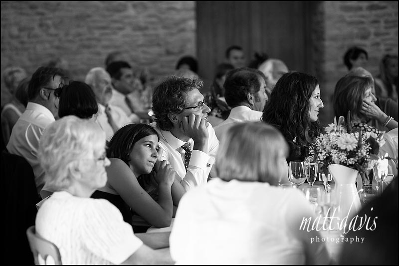 Documentary B&W wedding photos at Kingscote Barn during wedding speeches