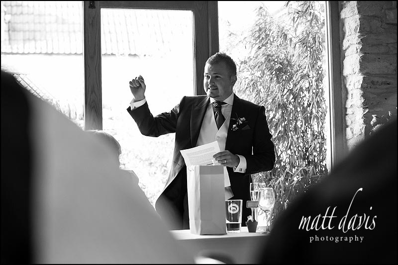 Black and white wedding photos at Kingscote Barn during wedding speeches