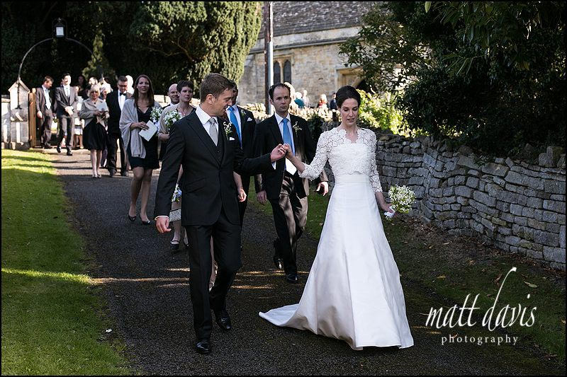 wedding couple leaving St Mary's church in Barnsley, Gloucestershire