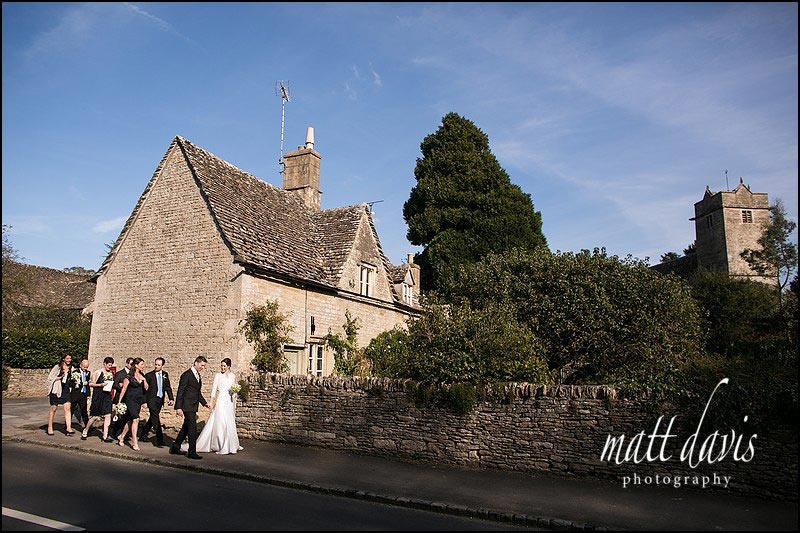 wedding couple walking to Barnsley House  from St Mary's Church