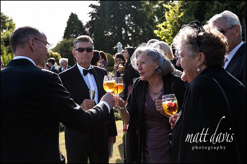 Wedding guests during the drinks reception outside at Barnsley House