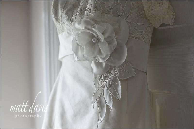 white flower detailing on wedding dress with sash