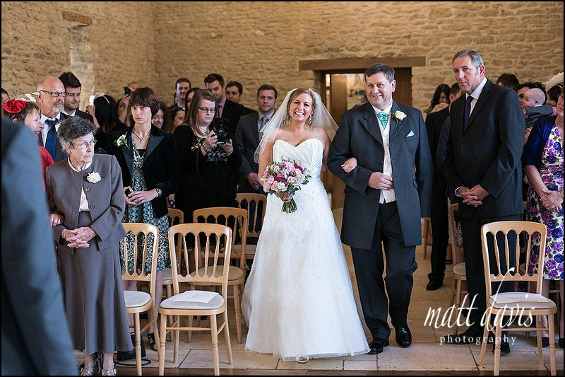Bride walking down aisle at Kingscote Barn