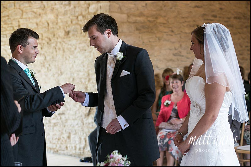 Best man presents rings during Kingscote Barn wedding ceremony