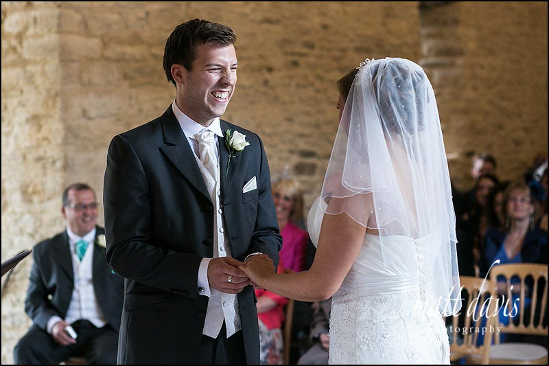 Happy groom as he puts ring on brides finger