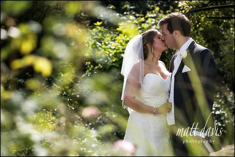Couple kiss at Kingscote Barn wedding