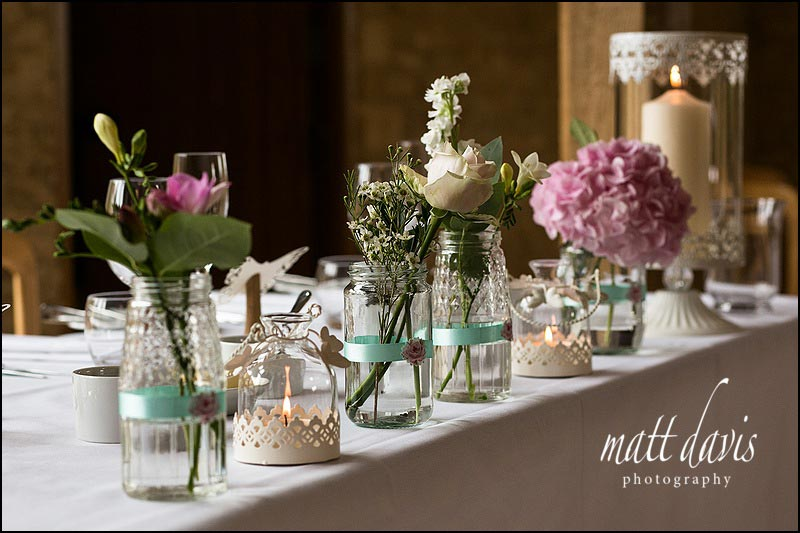 Vintage flowers in Jam Jars at Kingscote Barn wedding