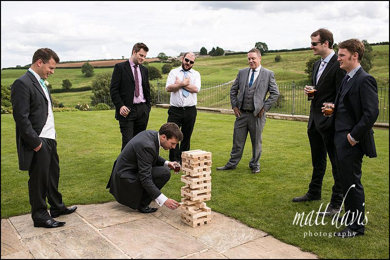 Kingscote Barn wedding photographer capture giant Jenga being played on the lawn