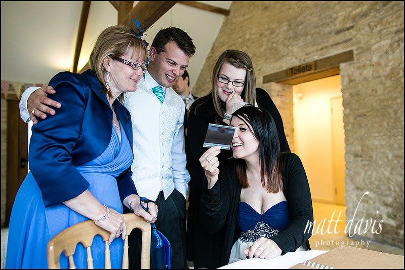 Wedding guests looking at polaroid photo taken at Kingscote Barn