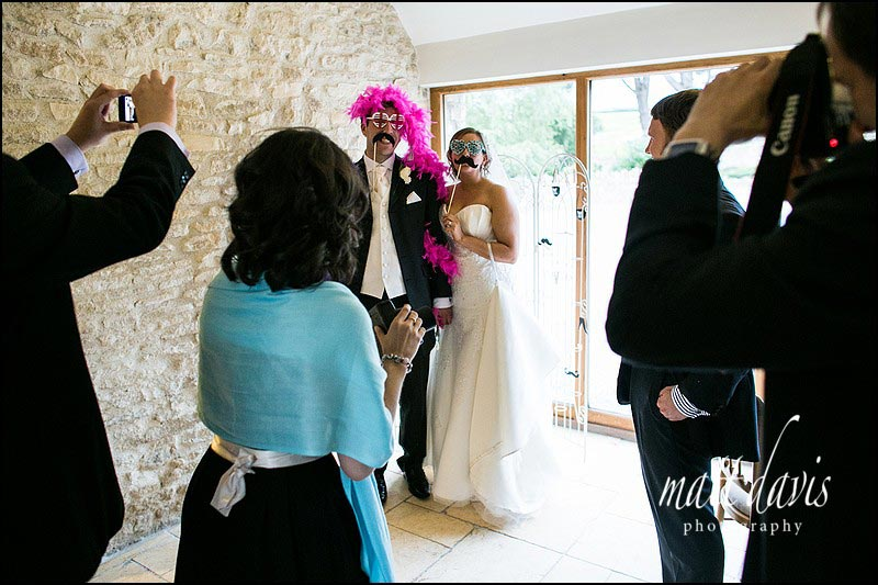 bride & groom dressed up in funny props at a Kingscote Barn wedding