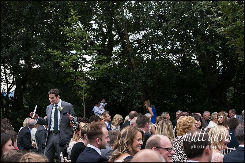 Groom & guests waiting at an outdoor wedding ceremony