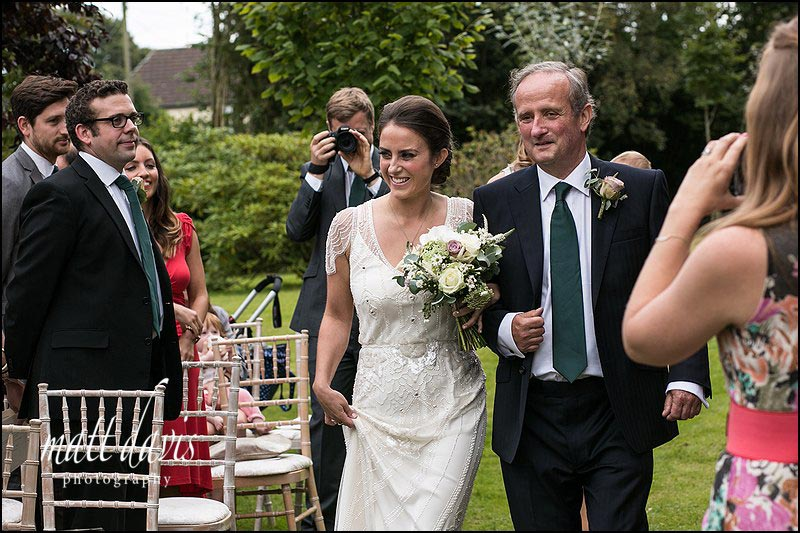 Bride and father walking down aisle during outdoor wedding ceremony