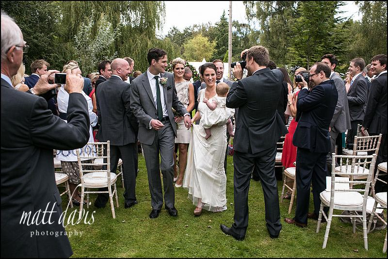 Guests taking photos as bride and groom walk down aisle at outdoor wedding ceremony