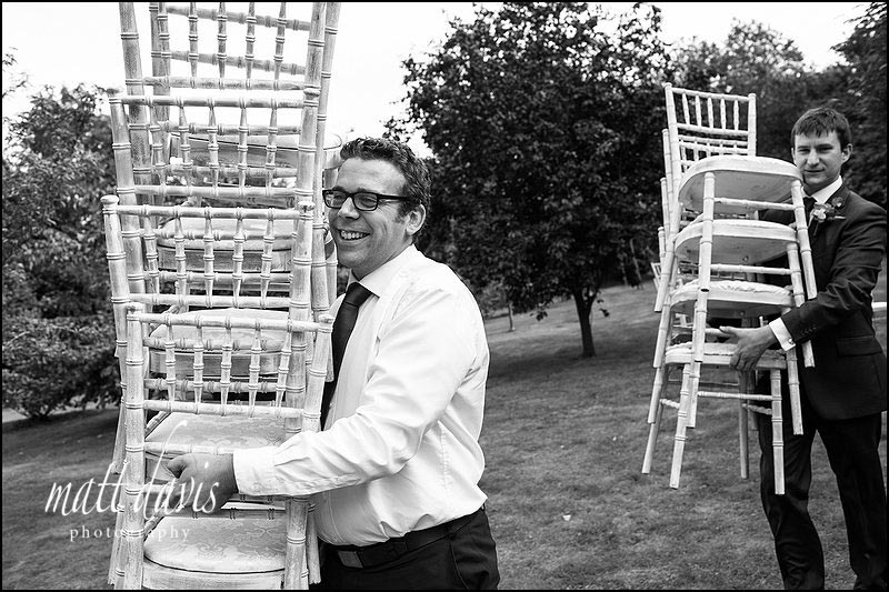Wedding guests carrying chairs into the wedding marquee